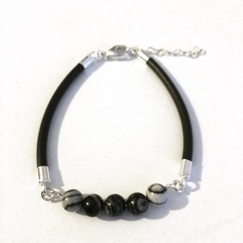 Armband i svart gummi med detaljer i sterling silver och 5 st släta runda  pärlor i black silk stone. Armbandets storlek går att justera. d2ea28de6dd7d